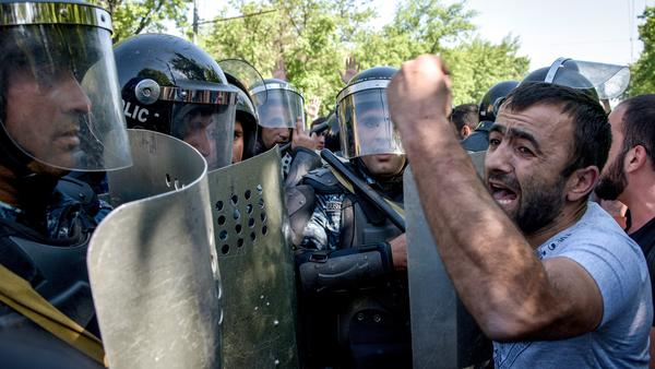 A man confronts Armenian riot police officers during an opposition rally Monday in the capital, Yerevan. Thousands of people gathered to protest a move by the ex-president to maintain his hold on power.