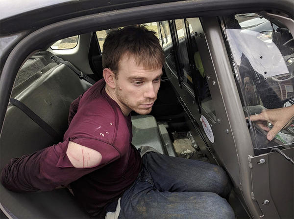The Metro Nashville Police Department released a photo showing Travis Reinking in the back of a police car moments after being arrested on Monday.