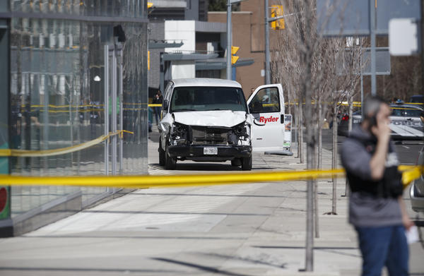 Police inspect a van used in a rampage that left at least 10 people dead Monday in Toronto.