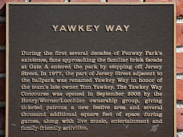 A plaque describing Yawkey Way is pictured on the side of Fenway Park. The street pays homage to former Red Sox owner Tom Yawkey, who kept his team all-white longer than anyone else, passing up chances to hire future Hall of Famers Jackie Robinson and Willie Mays along the way.
