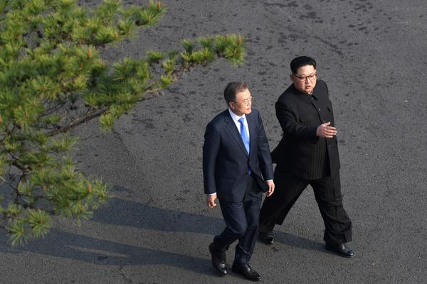 South Korea's President Moon Jae-in (left) and North Korea's leader Kim Jong Un walk together after a tree-planting ceremony at the truce village of Panmunjom on Friday. Both leaders sat down to a historic summit after shaking hands over the Military Demarcation Line that divides their countries.