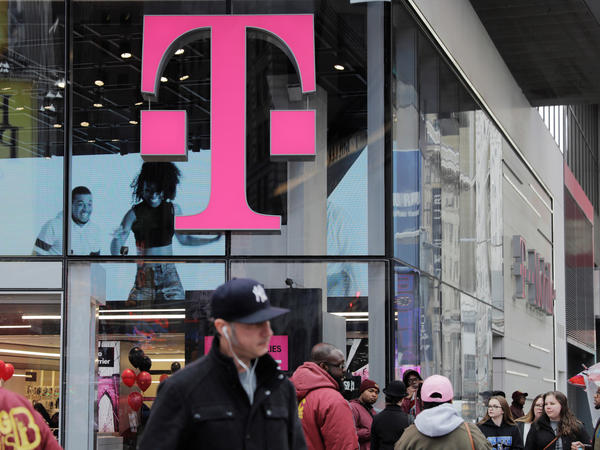 Pedestrians walk past a T-Mobile store in New York City on Friday. Sprint and T-Mobile are seeking to merge, but the proposed deal sill requires regulatory approval.