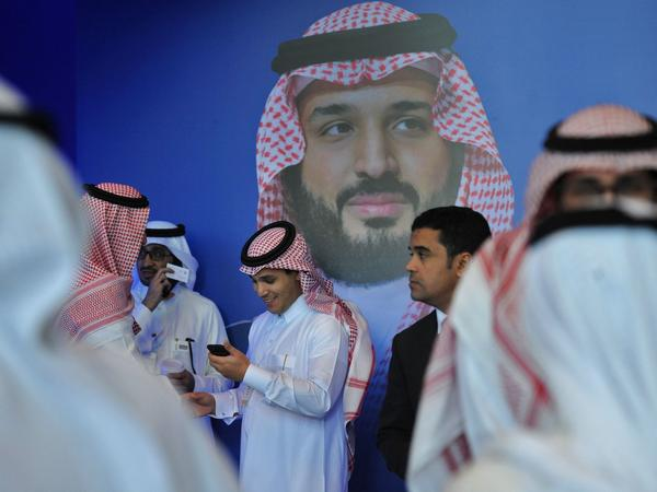 Saudi men chat in front of a poster of Saudi Crown Prince Mohammed bin Salman at an international gathering in Riyadh in November. Social liberalization is being driven by the 32-year-old crown prince, who launched an ambitious plan called Vision 2030 to open the kingdom, diversify its economy and create jobs, especially for young people.