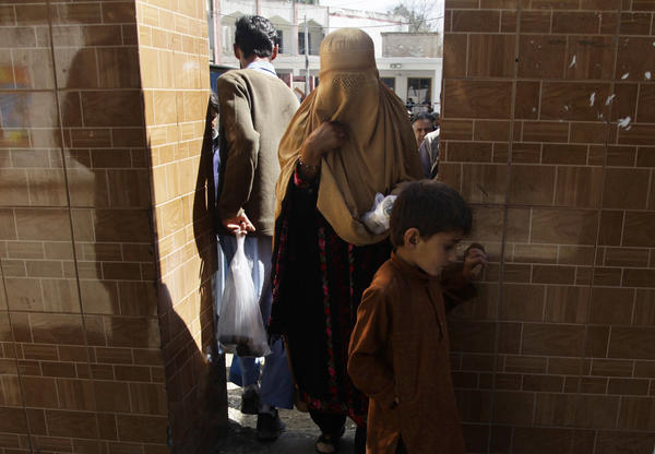 """Noorshad Begum, seeking legal help, walks through the gate of the court complex with her son. """"My husband married another woman,"""" she says. """"He abandoned me. I have five children. He doesn't bother to ask about us."""""""