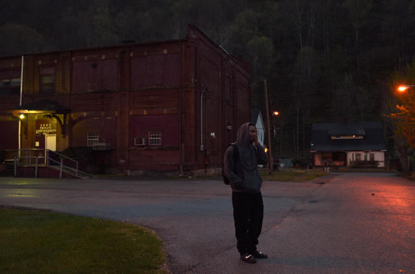 Akal waits at dawn for his aunt to pick him up and take him to work at a factory.