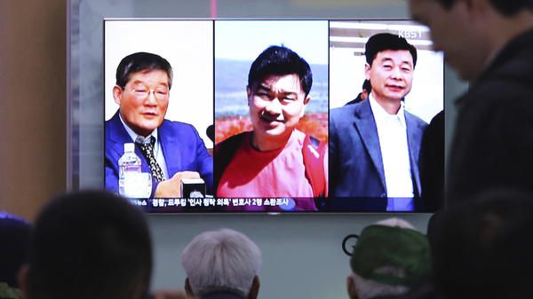 People watch a TV news report in Seoul, South Korea, on May 3, as the screen shows portraits of three Americans detained in North Korea: Kim Dong Chul (left) Tony Kim and Kim Hak-song (right). Three American prisoners in North Korea were released into U.S. custody on Wednesday, according to President Trump.