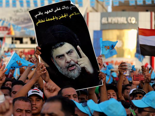 Followers of Shiite cleric Muqtada al-Sadr, seen in the poster, take part in a campaign rally in Baghdad's Tahrir Square on May 4.