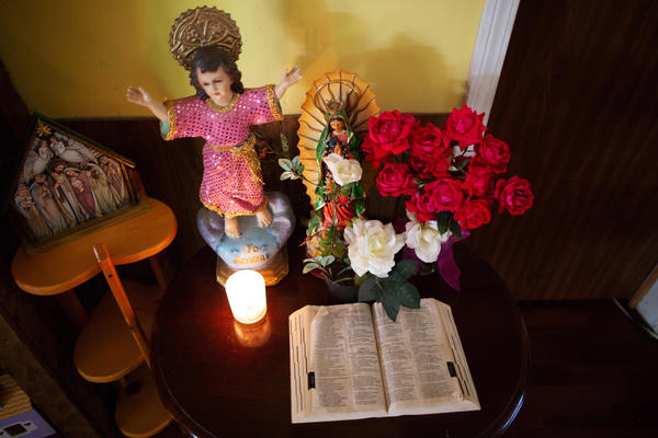A Bible and other religious symbols sit on a table inside Ms. A.B.'s home.
