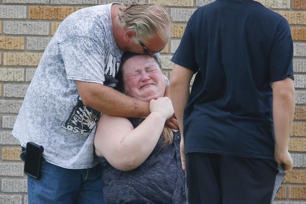 A man hugs a woman outside the Alamo Gym where parents wait to reunite with their kids following a shooting at Santa Fe High School.