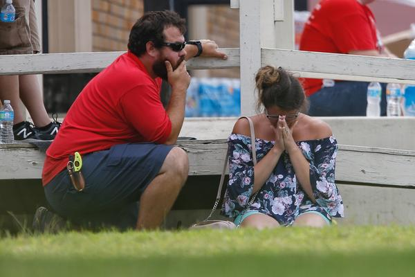 A woman prays in the grass outside the Alamo Gym where parents wait to reunite with their kids following a shooting.