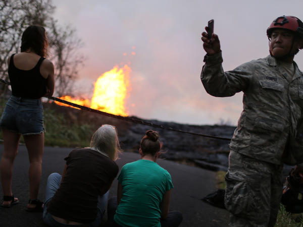 A U.S. National Guard soldier takes photos as lava erupts and flows from a Kilauea fissure in Leilani Estates on Wednesday.
