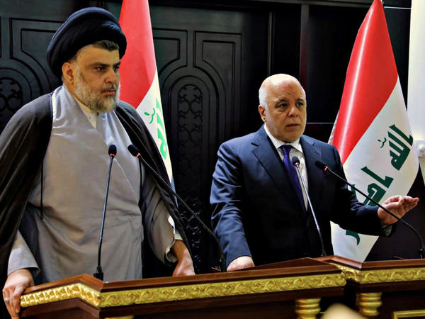 In this photo provided by the Iraqi government, Iraqi Prime Minister Haider al-Abadi (right) and Shiite cleric Muqtada al-Sadr hold a press conference in Baghdad on May 20. Sadr's coalition won the largest number of seats in Iraq's parliamentary elections.