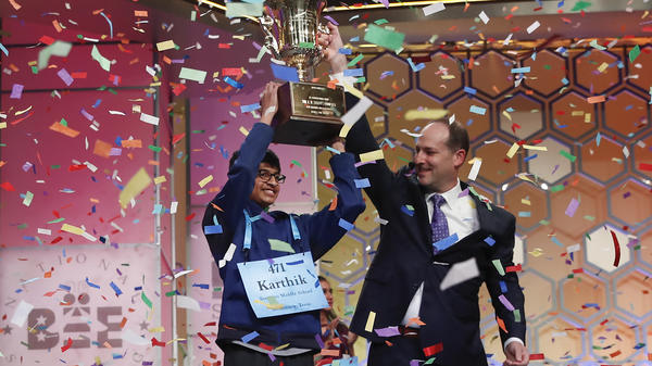 Karthik Nemmani, 14, of McKinney, Texas, holds the Scripps National Spelling Bee Championship trophy with Adam Symson, the Scripps president and chief executive officer.
