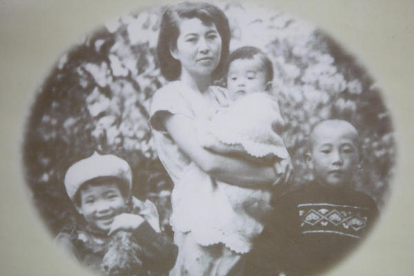 Hirono, pictured at left, with her mother, Laura, who is holding her brother Wayne. Her brohter Roy is on the right.
