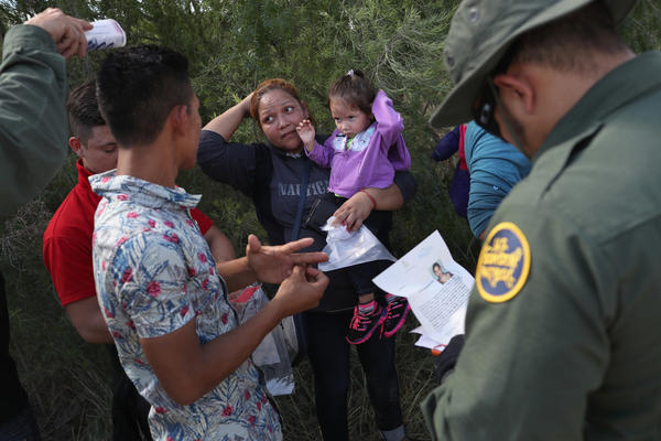 U.S. Border Patrol agents ask a group of Central American asylum seekers to remove hair bands and wedding rings before taking them into custody on June 12, near McAllen, Texas.