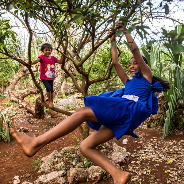 Gelmy, 9, and sister Alexa, 4, climbing trees in the backyard of their family home in the Yucatan Peninsula.