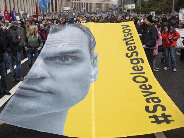 Protesters hold a poster with the image of Ukrainian prisoner Oleg Sentsov during an opposition rally organized by Free Russia in Moscow, on June 10.