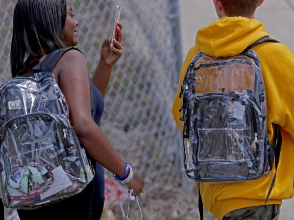 Students wear clear backpacks outside Marjory Stoneman Douglas High School in Parkland, Fla., on Monday. The bags are one of a number of security measures the school district has enacted as a result of the Feb. 14 shooting at the school that killed 17.