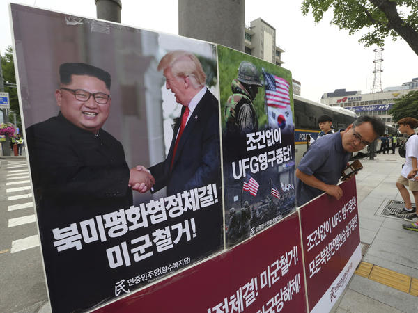 A photo of President Trump and North Korean leader Kim Jong Un is on display as a member of People's Democratic Party stands in opposition of military exercises between the United States and South Korea near the U.S. embassy in Seoul on Tuesday.