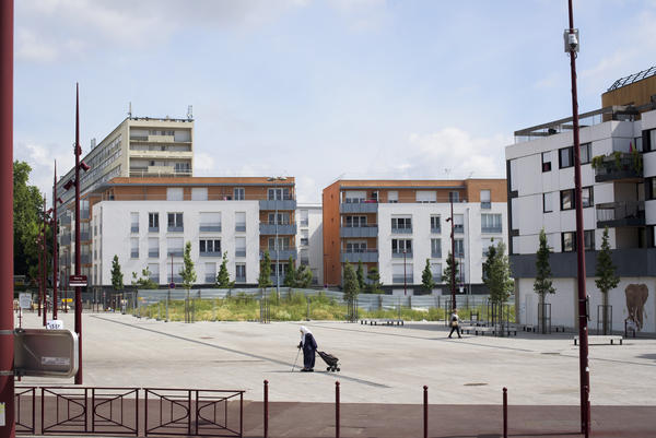 A woman walks through a square as an old housing project looms behind newer buildings in Bondy, a suburb of Paris, France.