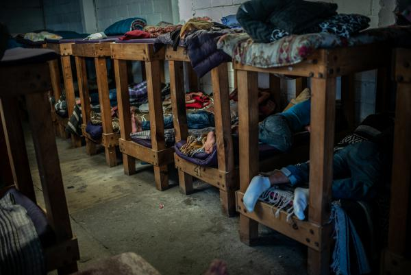 Central American migrants rest in a shared room for men only at the migrant and refugee center.