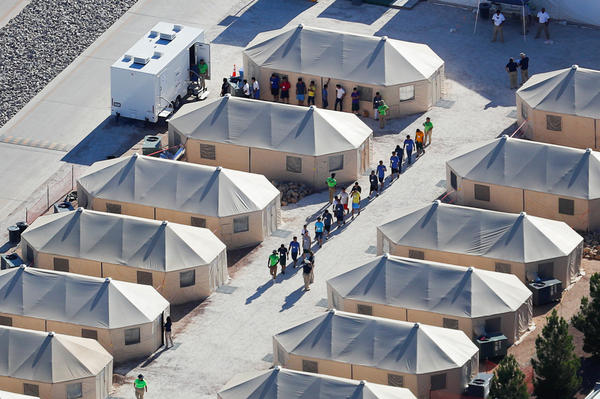 "Migrant children now housed in a tent encampment under the Trump administration's ""zero tolerance"" policy are shown walking in single file at the facility near the Mexican border in Tornillo, Texas, on June 19."
