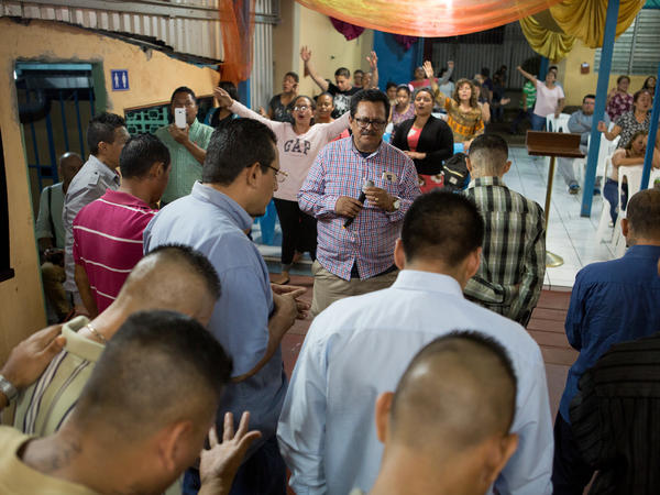 The Rev. Nelson Moz, churchgoers and ex-gang members pray together at Eben-ezer in San Salvador.