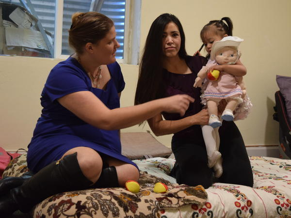 Sandra Lopez holds her daughter, Areli, next to Rev. Shawna Foster in the basement of the Two Rivers Unitarian Universalist parsonage in Carbondale, Colo.