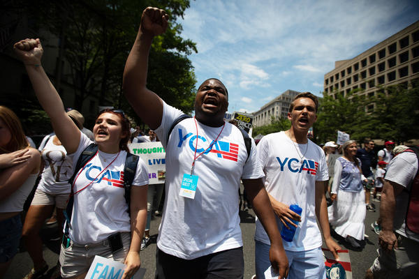 """""""Families Belong Together"""" protesters chanted in unison as they marched toward the Capitol."""