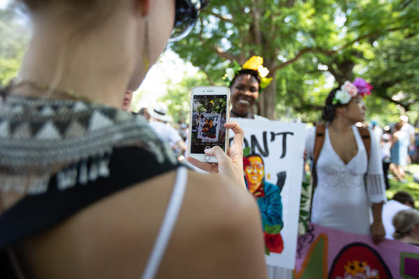 """Members of the Omi Collective take photos of one another holding signs, calling their protest a tribute to women and an act of """"performance art."""""""