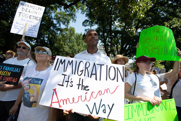 """A demonstrator listens to the event's speakers at Saturday's """"Families Belong Together"""" rally in Lafayette Square Park."""