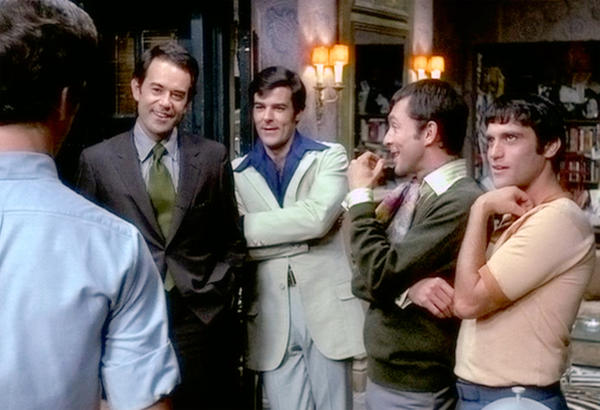 The original production of <em>The Boys in the Band </em>was adapted into a 1970 movie. In this film still, Laurence Luckinbill (playing the character Hank) stands in the jacket and tie on the left.