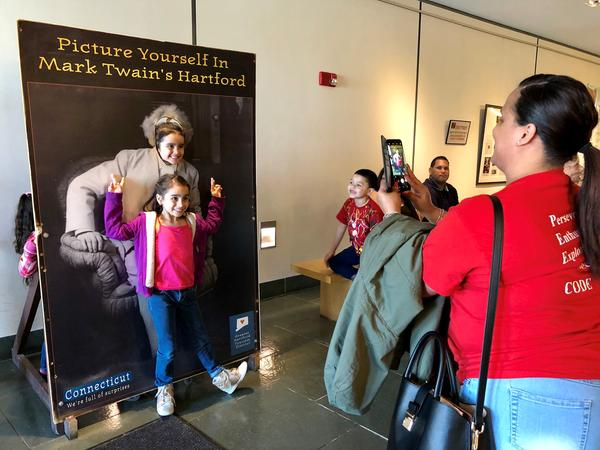 Sanchez School employee Sally Vazquez, right, takes a photo of Hartford students in the lobby of the Mark Twain House & Museum. Families displaced from Puerto Rico were invited to the American landmark.