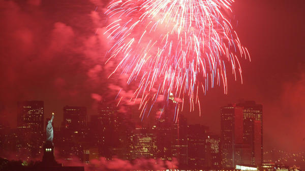 The sky surrounding the Statue of Liberty in New York is lit red by a firework in 2005. Nearly all the fireworks consumers will purchase this year — and 70 percent of those used by professionals — are manufactured in China.