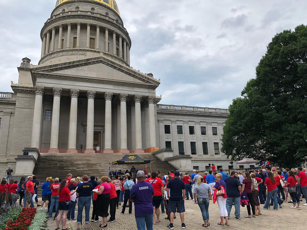 Teachers, public employees and their supporters gather outside the state Capitol's gold dome in Charleston, W.Va.