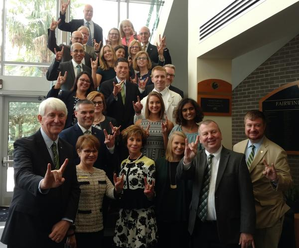 USF officials, led by Provost Ralph Wilcox, first row left, and System President Judy Genshaft, first row third from left, celebrate Thursday in Orlando after a FL Board of Governors committee approved USF as a preeminent university.