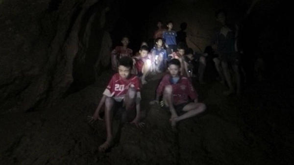 The boys and their soccer coach, seen in partially flooded cave in northern Thailand on Monday. Found after more than a week of searching, they are mostly in stable medical condition and have received high-protein liquid food, officials said Tuesday.