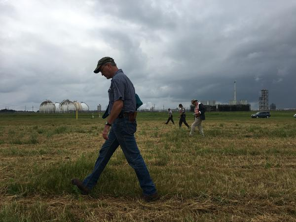 Officials from the Army Corps of Engineers walk across the Kenner Cemetery -- one of two cemeteries inside the Bonnet Carré  Spillway where the remains of formerly enlaved people are buried.
