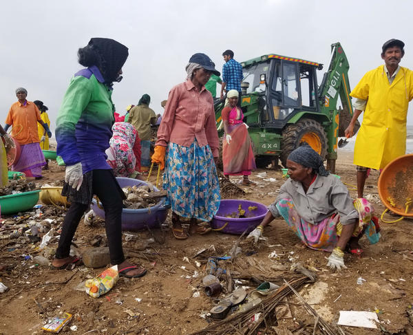 Volunteers and some municipal workers carry buckets of trash to a bulldozer on Mumbai's Versova Beach. Three years ago, a lawyer who lives near the beach, Afroz Shah, started a cleanup campaign on Facebook and Twitter.