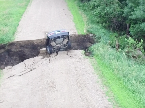 A screenshot from a video posted by the Renville County Sheriffs Office shows the aftermath of a car driving into a chasm in the road.