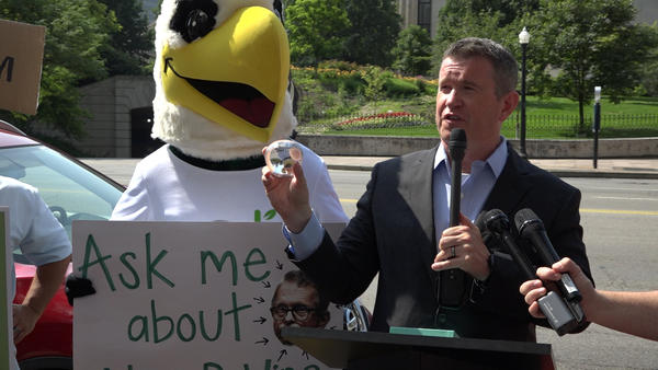 Former Rep. Steve Dyer, now with the progressive think-tank Innovation Ohio, holds an ECOT-branded Tiffany paperweight next to ECOT's mascot at a press conference Monday. The paperweight and mascot costume were auctioned off last month after ECOT closed.