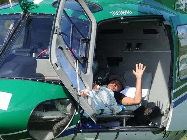 Brazilian striker Neymar waves on July 5, 2014, from inside the helicopter that transported him from Teresópolis, Rio de Janeiro state, to his residence in Guarujá after an injury.