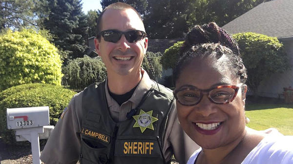 Oregon state Rep. Janelle Bynum poses with the Clackamas County sheriff's deputy who responded to a call from someone who said Bynum was casing the neighborhood. The legislator said she was going door to door talking to constituents.