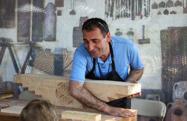 "At the Smithsonian Folklife Festival in Washington, D.C., Vahagn Amiryan of Armenia prepares to carve an inscription on a block of wood that would sit atop the ""mother pillar"" inside a traditional house in his country."