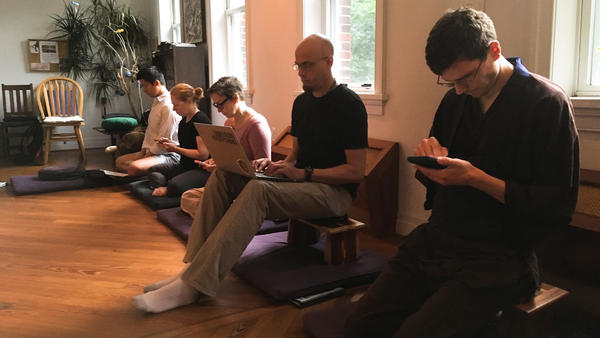 Participants check in on social media and send texts on their phones during a screen mindfulness workshop at the All Beings Zen congregation in Washington, D.C.