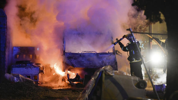 A firefighter works to extinguish a burning vehicle in Nantes, France, on Tuesday. Days of unrest have plagued the city after a police officer fatally shot a motorist at a checkpoint.
