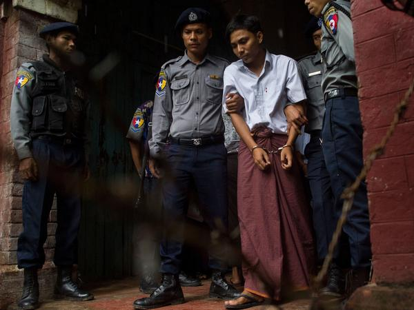 Kyaw Soe Oo, 28, leaves the Yangon courthouse in May, handcuffed and flanked by police officers.