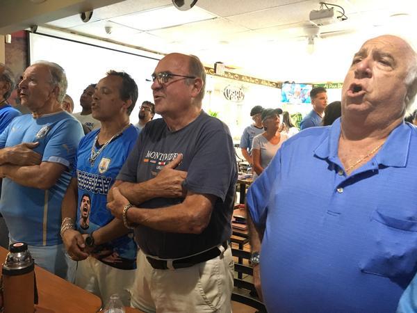 Men singing the Uruguayan national anthem before the match began.