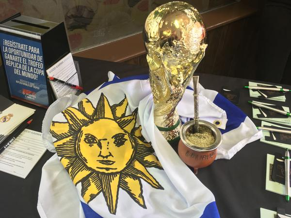 The Uruguayan flag wrapped around a model of the FIFA World Cup trophy, and mate, a traditional Uruguayan herb drink.