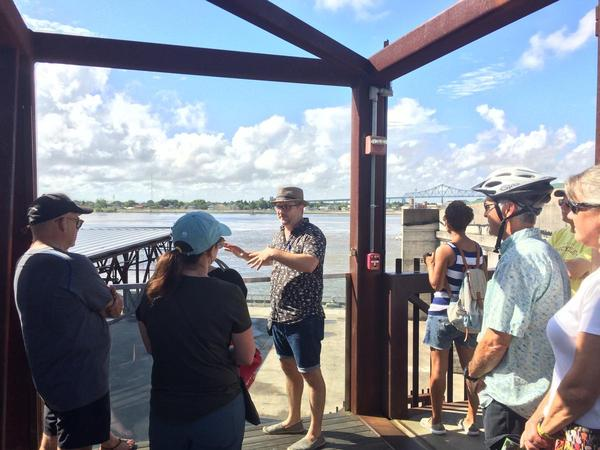 Looking out over Crescent Park, guide Cassady Fallon Cooper describes the role of the Mississippi River to tour participants.